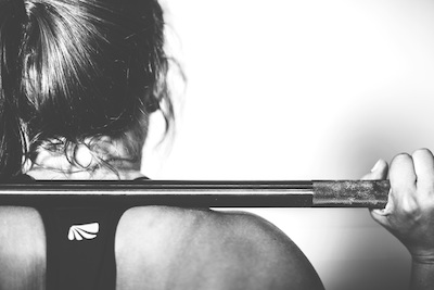 Monochrome image of a woman's back holding a barbell